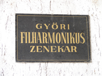 Photo of a plaque identifying the Győr Philharmonic Orchestra (Győri Filharmonikus Zenekar) in an entryway into the orchestra's home, the Janos Richter Hall. Győr, Hungary; (21 September 2007)