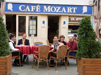 "Friends and their composer gathered at Győr's Mozart Café for ""snacks"" after Alma's rehearsal (L to R) Connie Kotis, Dávid Zsolt Király, Szidónia Juhász, Judi Howle, Harold Schiffman [and unidentified patron of the restaurant]. Győr, Hungary (15 October 2008)"
