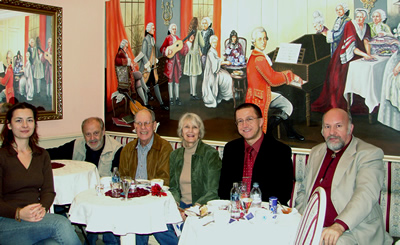 Principals involved in October's recordings and performance, enjoying  pastries at Győr's Mozart Café, upon completion of their work. (L to R) Szidónia Juhász, Mátyás Antal, Harold Schiffman, Jane Perry-Camp, Dávid Zsolt Király, István Biller; W.A. Mozart, at the keyboard. Győr, Hungary (20 October 2008) Photograph by a kind and skilled but unnamed server at the Mozart Café
