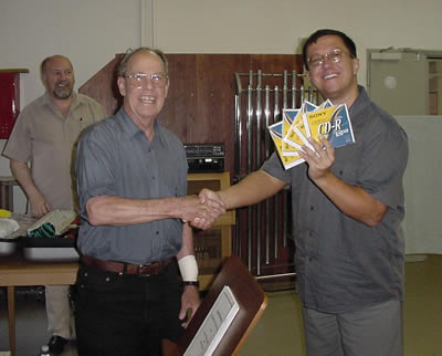 Photo of Dávid Zsolt Király handing Harold the edited and mastered CDs containing the newly recorded Alma (2002), Prelude and Variations for Chamber Orchestra (1970) [recorded in 1998], Chamber Concerto No. 2: In Memoriam Edward Kilenyi (2000) with recording engineer István Biller looking on, Győr, Hungary (17 June 2007)