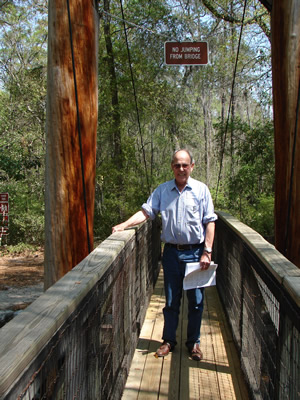"Harold Schiffman, having arrived at the 2009 Suwannee Banjo Camp, walks across the Santa Fe River and cheerfully obeys the bridge's sign: ""NO JUMPING FROM BRIDGE."" Suwannee Banjo Camp, O'Leno State Park, Florida (20 March 2009)"