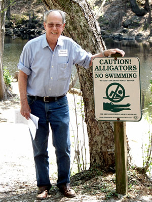 "Harold Schiffman, strolling along the Santa Fe River bank, likewise cheerfully obeys this sign:  ""CAUTION!  ALLIGATORS -- NO SWIMMING."" Suwannee Banjo Camp, O'Leno State Park, Florida (20 March 2009)"