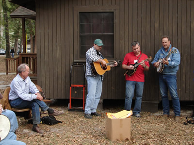 "Suwannee Banjo Camp's class ""Clawhammer Back-Up from Scratch"" under the tutelage of faculty member Mark Johnson, here seen demonstrating what session's name means.  (L to R)  Harold Schiffman, student; Danny Smith, guitar; Scott Anderson, mandolin; Mark Johnson, banjo. Suwannee Banjo Camp, O'Leno State Park, Florida (21 March 2009)"